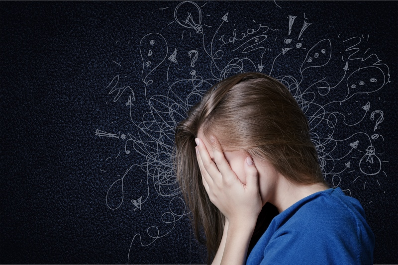 Confused woman having difficulty learning with hands over face and images behind on blackboard