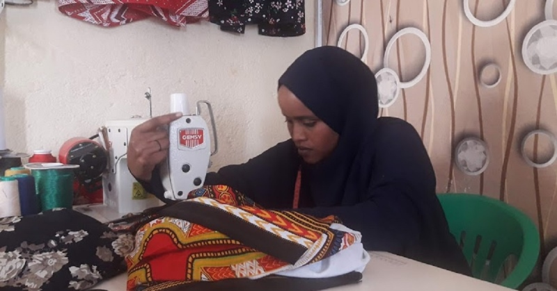 A woman at the sewing coop in Somalia creating an item of clothing